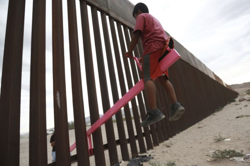 CORRECTS THE FIRST NAME OF THE PROFESSOR TO RONALD, NOT RONALDO AND THE LAST NAME OF THE PHOTOGRAPHER TO CHAVEZ, NOT TORRES - A child plays seesaw installed between the border fence that divides Mexico from the United States in Ciudad de Juarez, Mexico, Sunday, July 28, 2019. The seesaw was designed by Ronald Rael, a professor of architecture in California. (AP Photo/Christian Chavez)
